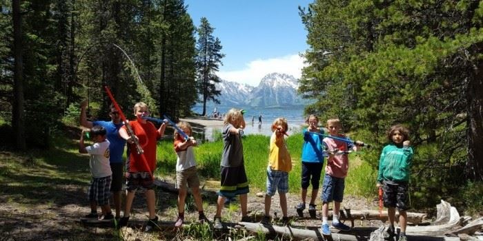 A group of kids standing in front of a lake and mountain range.